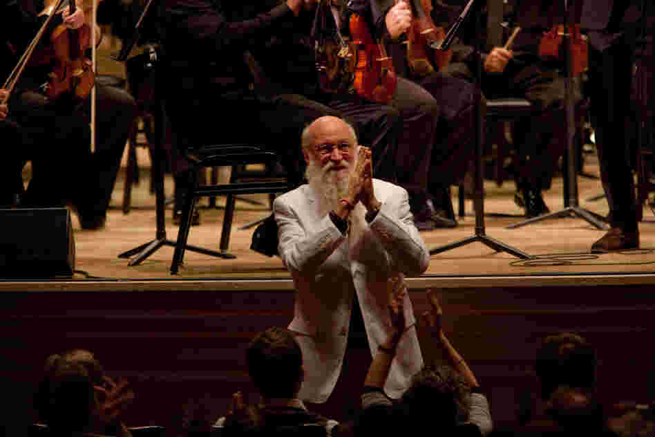 "Terry Riley accepting enthusiastic applause. He said that his concerto ""leaped into my consciousness as a very spontaneous work, full of the things in music that I find colorful, dynamic, beautiful, challenging, humorous, loving, friendly, joyous, stark and universally minded."""