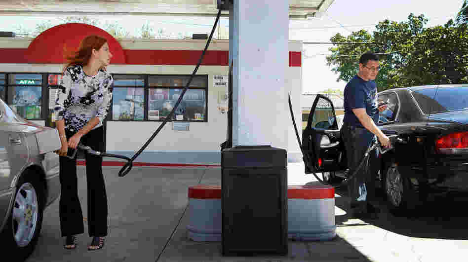 Mayeli Vasallo (left) and Jorge Monte pump gas in Miami in April. The average price of a gallon of gas has dropped 20 cents in the last month, to $3.73.