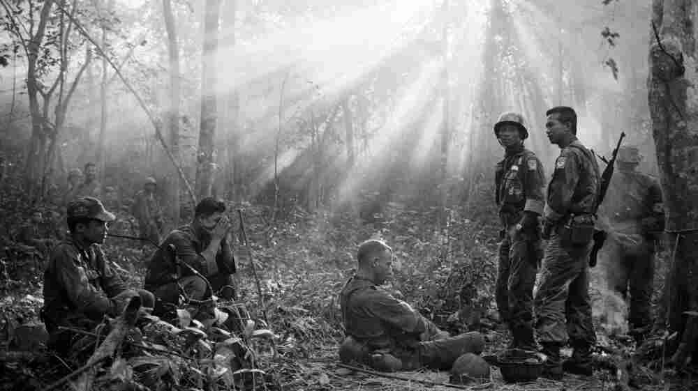 The sun breaks through dense jungle foliage as South Vietnamese troops, joined by U.S. advisers, rest after a cold, damp and tense night of waiting in an ambush position for a Viet Cong attack that didn't come, January 1965.