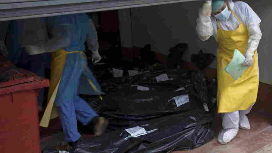 Morgue employees take in some of the bodies that were found Sunday.