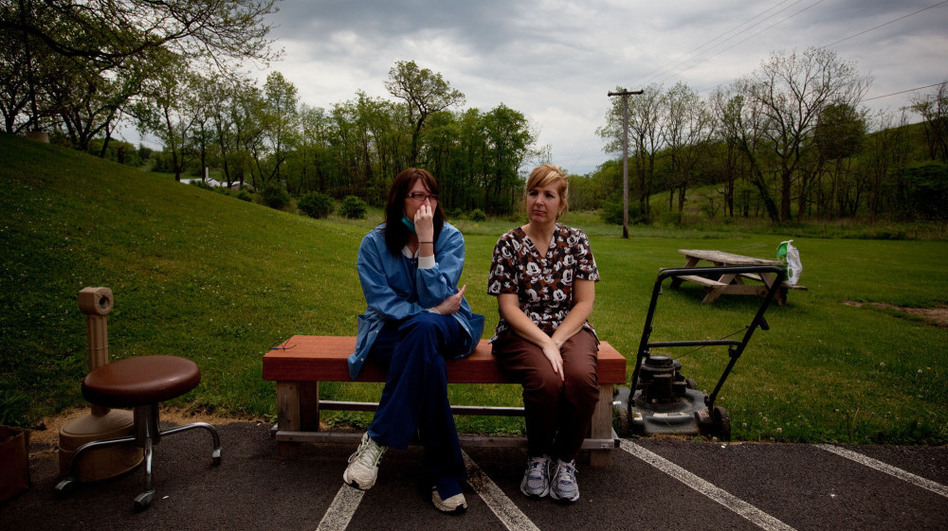 Michelle Salvini (left) and Terri DiCarlo take a break from work outside the Cornerstone Care clinic in Burgettstown, Pa. Mysterious fumes have repeatedly sickened clinic staffers, forcing them to evacuate the building several times.