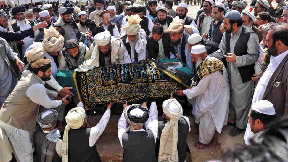 Officials and mourners prepare to place the coffin of Afghanistan High Peace Council and former Taliban leader Arsala Rahmani in a grave earlier today, in Kabul.