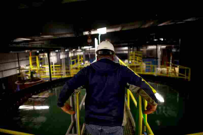 A worker crosses over a water-holding and skimming tank. In 2008, Eureka modified its technology to clean up the peculiar mix of gunk in frack water.