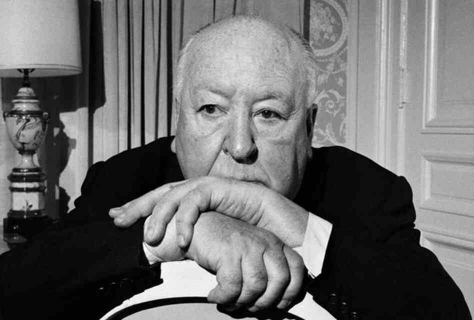 "April 1, 1976: Alfred Hitchcock in his suite at the St. Regis Hotel in New York. A note on the back of the photograph clarified who was directing the photo shoot: ""The picture showing Mr. Hitchcock creeping his way through the plant in his room was his idea."""
