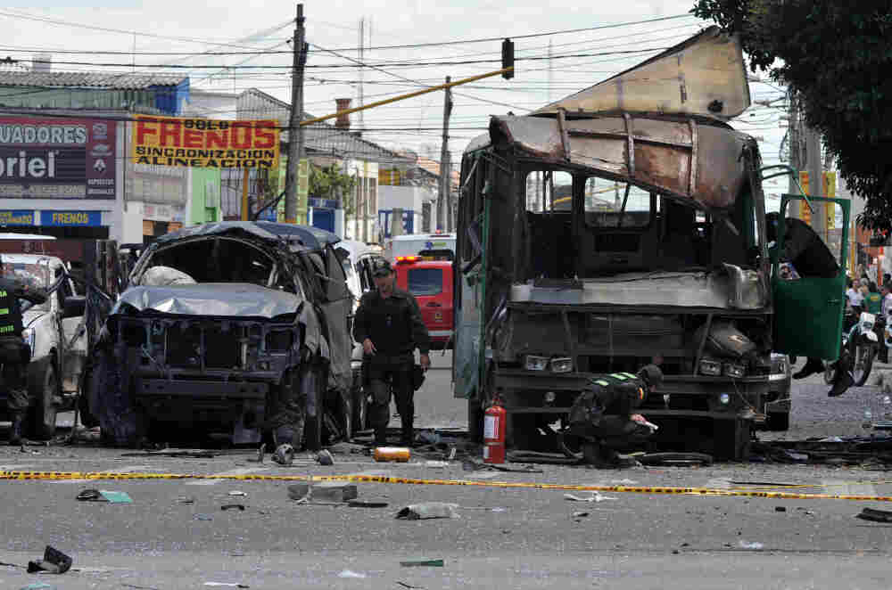Police officers inspect the remains of vehicles on Tuesday after an explosion ripped through a crowded area of Bogotá injuring at least 10 people according to the mayor's office.
