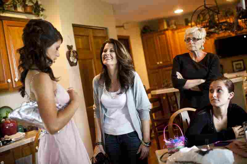 Kelley Hawkins (center) smiles at her daughter Carley (left) as her other daughter Chelsea (right) looks on, in their home in Harrisburg, Pa.