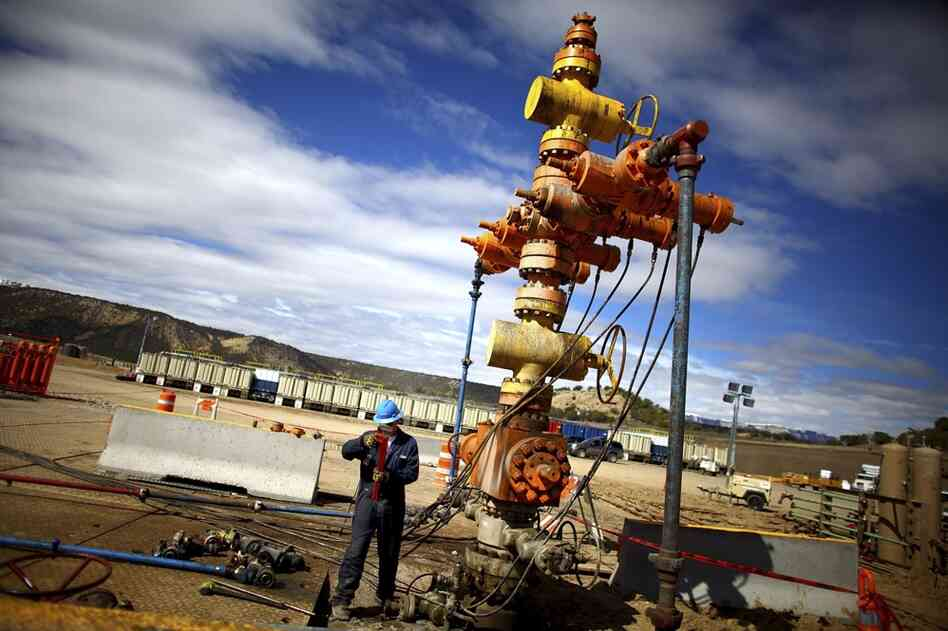 "A worker with Encana Oil and Gas stands near a natural gas ""Christmas tree"" used in the natural gas extraction process."