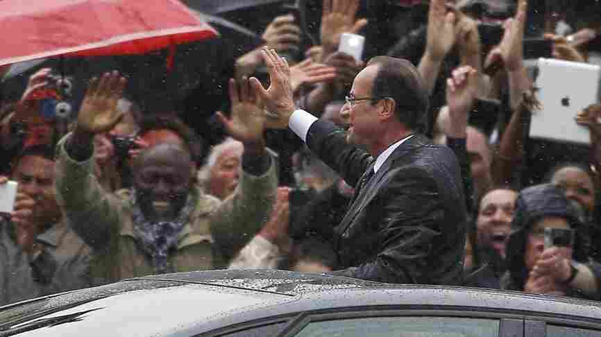 Francois Hollande stands up in his car Tuesday as he rides up the Champs-Elysees after taking the oath of office as the new president of France. Shortly afterward, he flew to Germany to meet with Chancellor Angela Merkel and discuss the continent's economic woes.