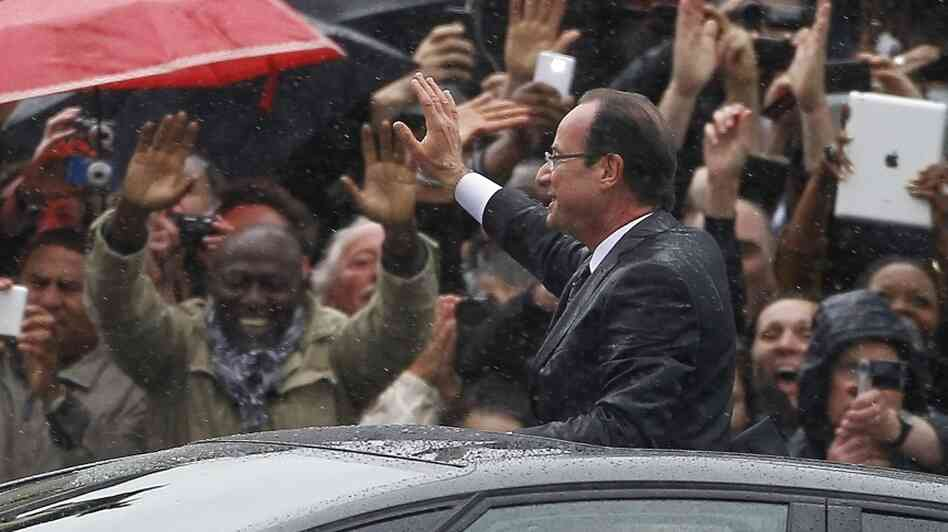 Francois Hollande stands up in his car as he rides up the Champs-Elysees after taking the oath of office as President of France.