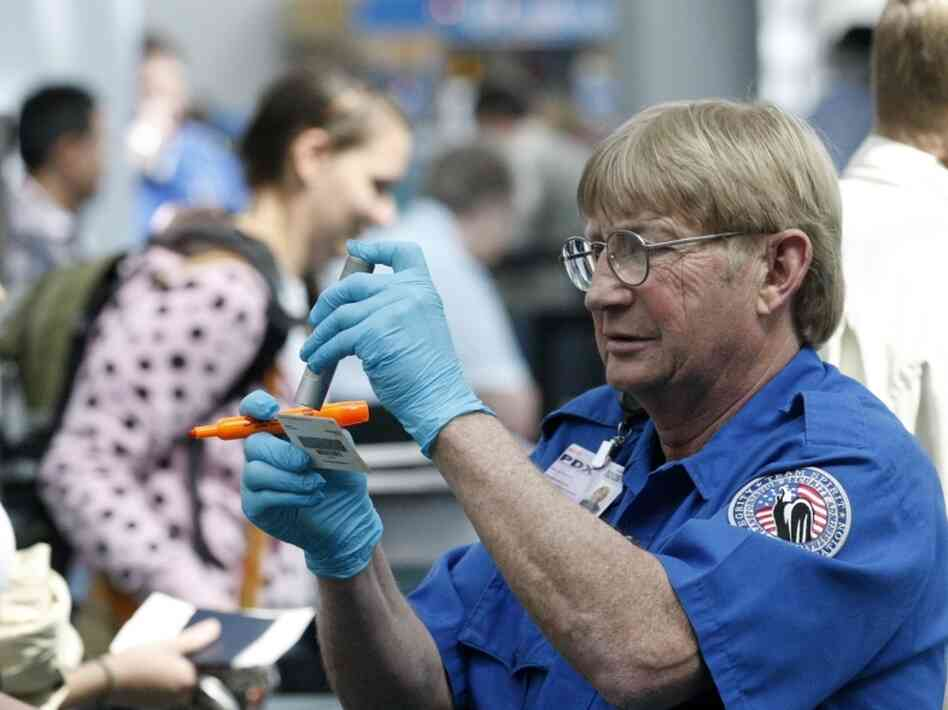 Despite the multiple layers of security at airports, terrorists still often target planes. But terrorism analysts say they are also concerned about soft targets. Here, a Transportation Security Administration agent looks at an identity card at the Portland International Airport earlier this month.