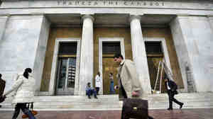 People walk past the Bank of Greece headquarters in Athens.