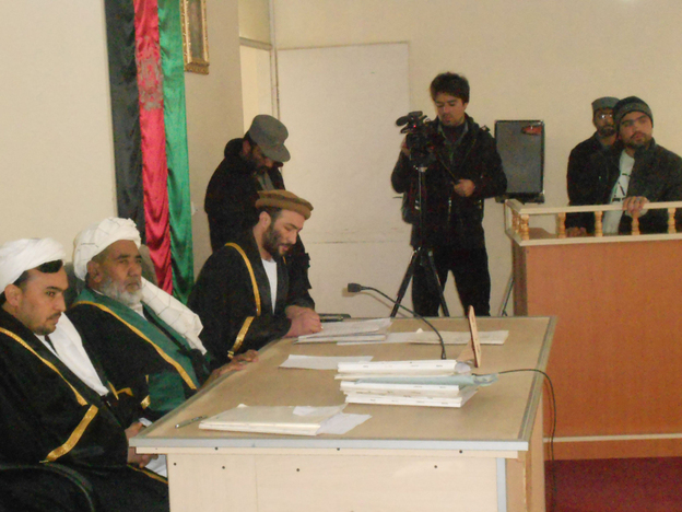 Afghanistan is struggling to develop its court system, and public trials are still relatively rare. Here, an Afghan man named Mahmood (standing, right) listens to a court judge during his trial in the western city of Herat on Jan. 24. He had photos of NATO bases in Afghanistan and was sentenced to 16 years for spying for Iran.