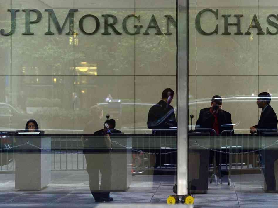People stand inside JPMorgan & Chase, Co. headquarters in New York on Monday May 14, 2012. President Barack Obama said Monday that the fact that JPMorgan Chase — one of the country's 'best managed' banks — could lose $2 billion in derivatives trades, showed the need for tighter banking regulation.