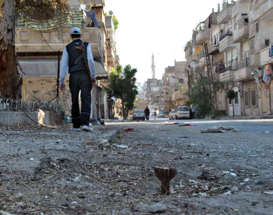 A Syrian rebel walks in Khaldiyeh neighborhood in Homs province, central Syria on Tuesday.