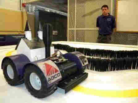 Brent Ware, a member of the robotics team at Kansas State, stands next to a planting robot that won a national competition.