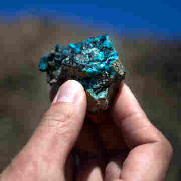 The mine at Oyu Tolgoi, Turquoise Hill in Mongolian, will be one of the world's largest copper mines in about five years. An employee holds up a small sample of the oxidized copper that gave the mine its name.