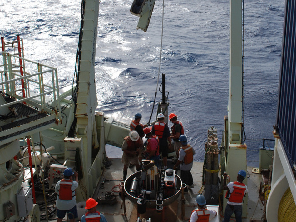 Researchers bring aboard a sea floor core sample. Researchers found 86-million-year-old bacteria living in the clay.