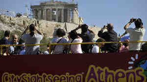 Greece depends heavily on tourism, but the economic crisis is driving away visitors like these ones photographing the Acropolis in Athens from the top of a tour bus last October.