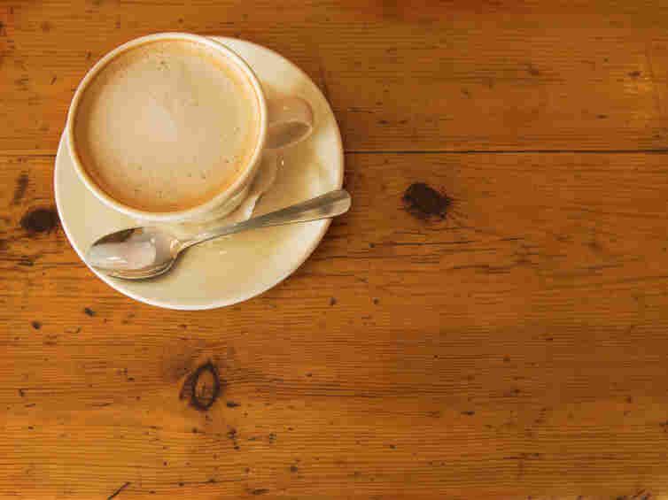A cup of coffee on a wooden table.