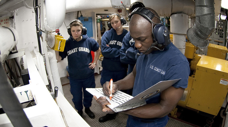 U.S. Coast Guard Academy Cadet Orlando Morel reviews a logbook in the generator room aboard the Coast Guard Cutter Eagle on June 23. Morel was 6 years old when he and his mother were rescued by the Coast Guard while leaving Haiti. Morel graduated Wednesday from the academy in New London, Conn.