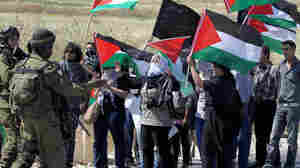 Israeli soldiers stand in front of Palestinian and foreign activists during a demonstration on the 64th anniversary of the creation of the state of Israel, at the Hawara checkpoint outside Nablus, West Bank, on Tuesday.