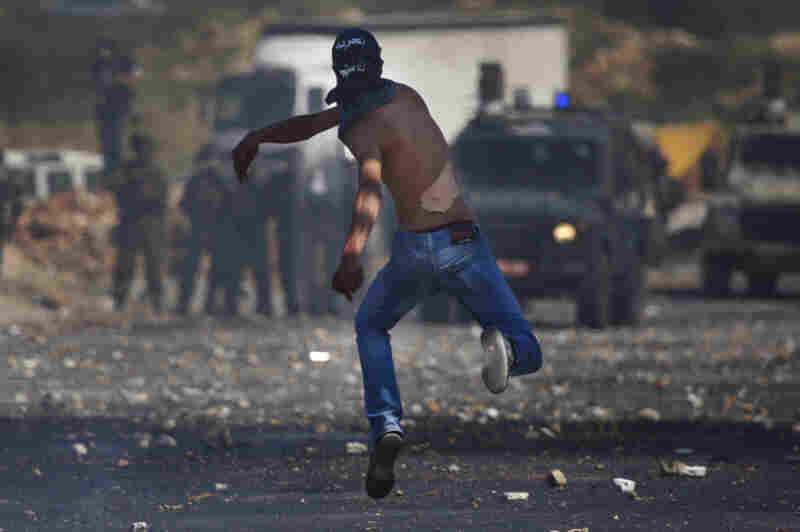 A masked Palestinian hurls a stone at Israeli troops during clashes outside the Ofer military prison, near the West Bank city of Ramallah on Tuesday, amid nakba demonstrations.