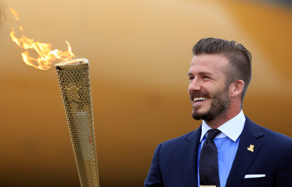 David Beckham holds the Olympic Flame as it arrives at RNAS Culdrose near Helston in Cornwall, England.