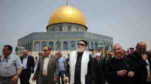 Egypt's grand mufti, Ali Gomaa (center, with scarf), visits the Al-Aqsa mosque in Jerusalem in April. The Dome of the Rock, which is part of the same compound, is shown behind him. Many Muslims have boycotted the site because Israel claims sovereignty. But Palestinian religious figures now say they welcome such visits, a move that has sparked controversy.