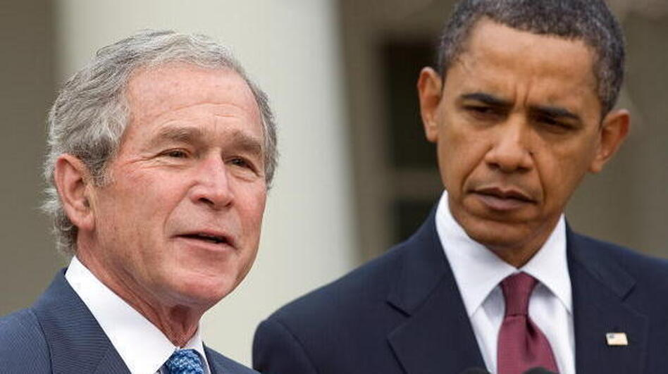 Former President George W. Bush, standing with President Obama, speaks about relief efforts in Haiti in January 2010. (AFP/Getty Images)