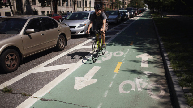 A cyclist rides on a bike lane on Prospect Park West, in the Brooklyn borough of New York City. Bike lanes of this type use parked cars to create a buffer zone from road traffic. (Getty Images)