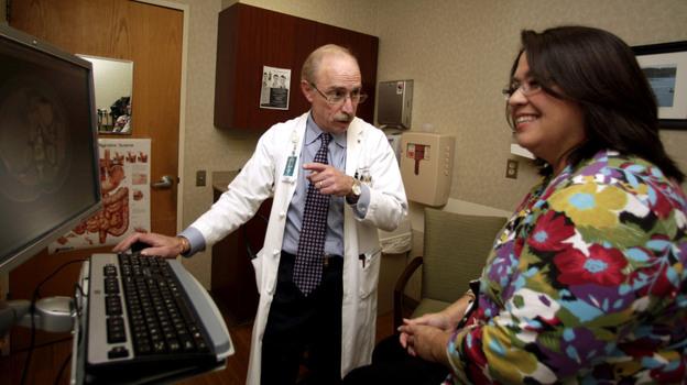 Dr. Paul J. Pockros, a liver specialist at Scripps Green Hospital in San Diego, talks with hepatitis C patient Loretta Roberts in Jan. 2011. (AP)