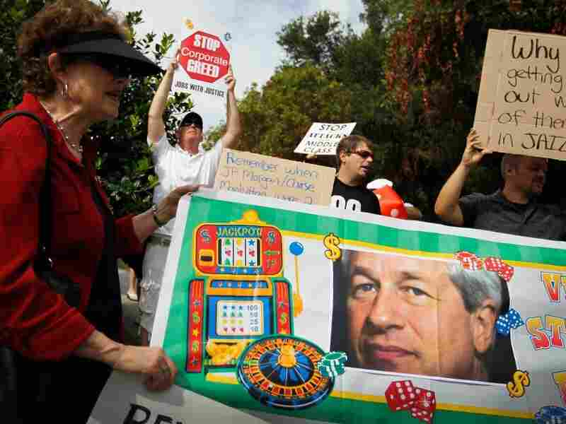 Protesters are seen behind a banner with a picture of JPMorgan Chairman and CEO James Dimon as they make themselves heard outside the building where a JP Morgan Chase shareholders meeting was taking place on May 15, 2012 in Tampa, Florida. The annual meeting is being held after JPMorgan last week disclosed a $2 billion-plus trading loss.