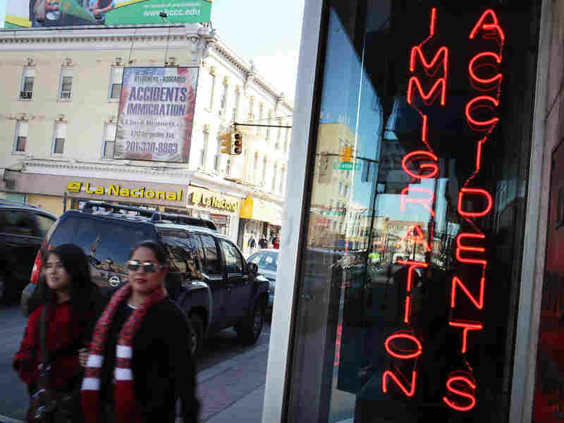 Hispanic residents walk by a law office in Union City, N.J., specializing in immigration in March. Union City is one of the state's largest cities, and has a Hispanic population of more than 80 percent.