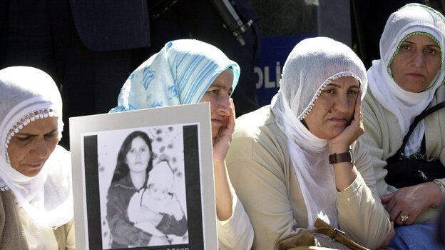 A woman holds a photo of Guldunya Toren, an unmarried mother