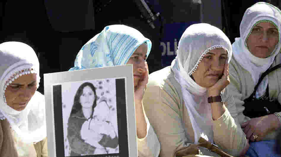 A woman holds a photo of Guldunya Toren, an unmarried mother allegedly killed by her brothers for having a child out of wedlock, outside parliament in Ankara, Turkey, in 2004. Her case prompted huge protests and forced Turks to realize that the justice system often fails to protect at-risk women.