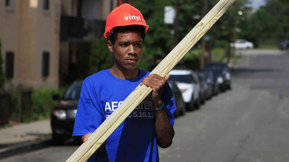 Domingo Williams, a participant in the Sasha Bruce Youthwork program, gathers wood to help rebuild a gutted house in the Southeast neighborhood