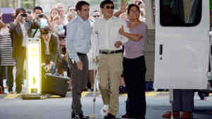 Chinese legal activist Chen Guangcheng, center, arrives at Washington Square Village on the campus of New York University on Saturday in New York. Chen escaped from his village in April and was given sanctuary inside the U.S.