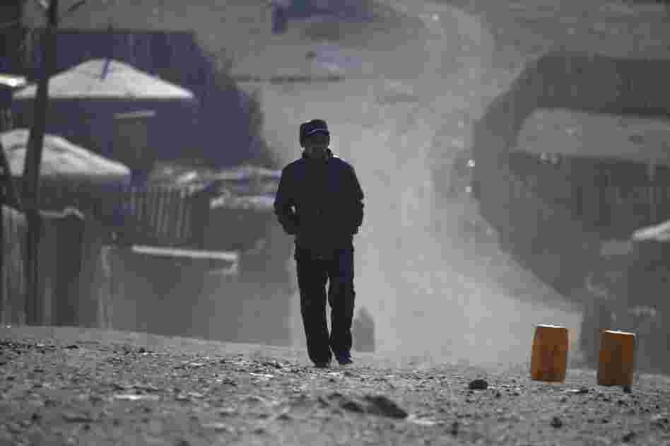 A ger district resident walks the dusty streets on the outskirts of Ulan Bator. As Mongolia's mining industry continues to grow, the future of the country's traditional ways is unclear.