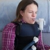 Katie Beckett fits herself with a vibrating vest that helps clear mucous from her lungs.