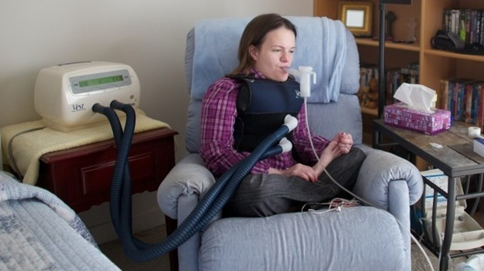 Katie Beckett fits herself with a vibrating vest that helps clear mucous from her lungs. A nurse comes over to her apartment in Cedar Rapids to help her do this twice a day.  On the wall to the right are pictures of Katie as a child with Ronald Reagan.   This story starts twenty-nine years ago with an angry President Ronald Reagan.    We just recently received word of a little girl who has spent most of her life in a hospital.     The little girl in the hospital was three-year-old Katie Beckett. Because of a brain infection, she needed to be hooked to a ventilator at night to breathe. Her parents wanted her home. Her doctors said she'd be better off at home. And it'd be cheaper, too: Just one-sixth the cost. (NPR)