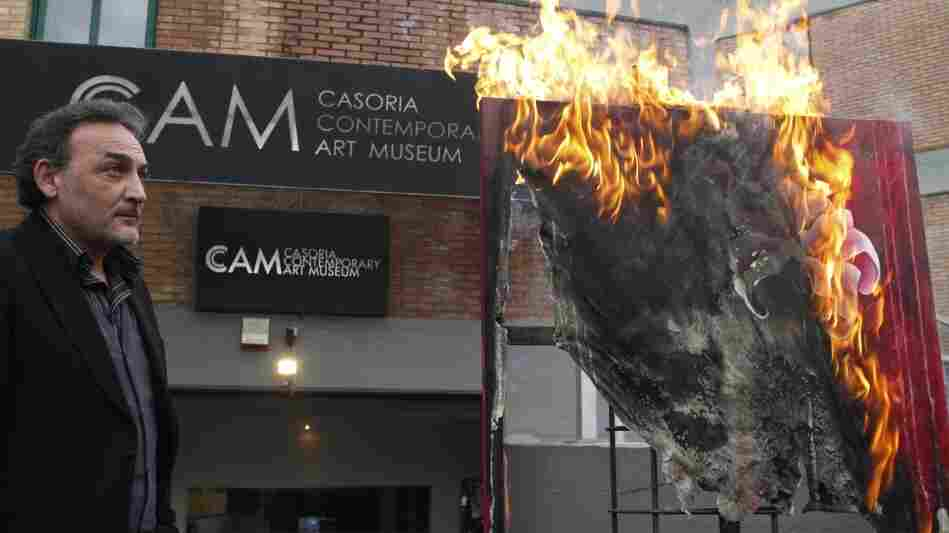 Antonio Manfredi, director of the Museum of Contemporary Art in Casoria, Italy, burns an artwork by French artist Severine Bourguignon. Manfredi is burning the museum's works to protest deep cuts to the arts.