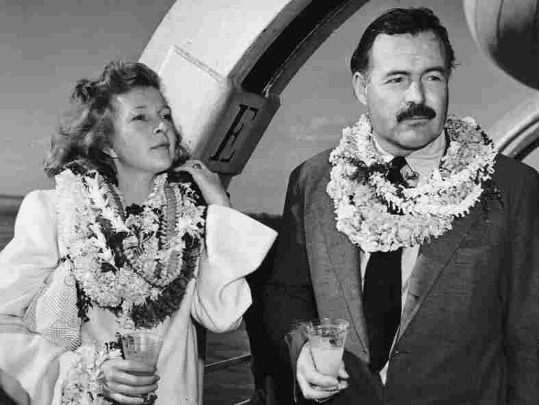 1941: Hemingway and Gellhorn, married in 1940, stand on deck aboard a ship, wearing leis and holding cocktails. They divorced in 1945.