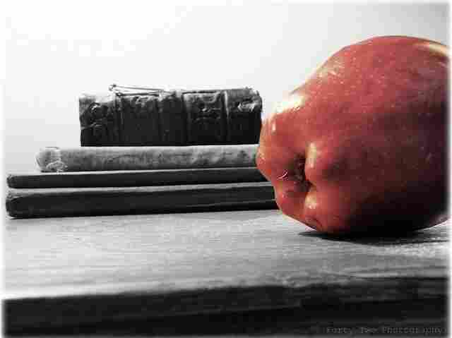 An apple rests on a desk next to a pile of books.
