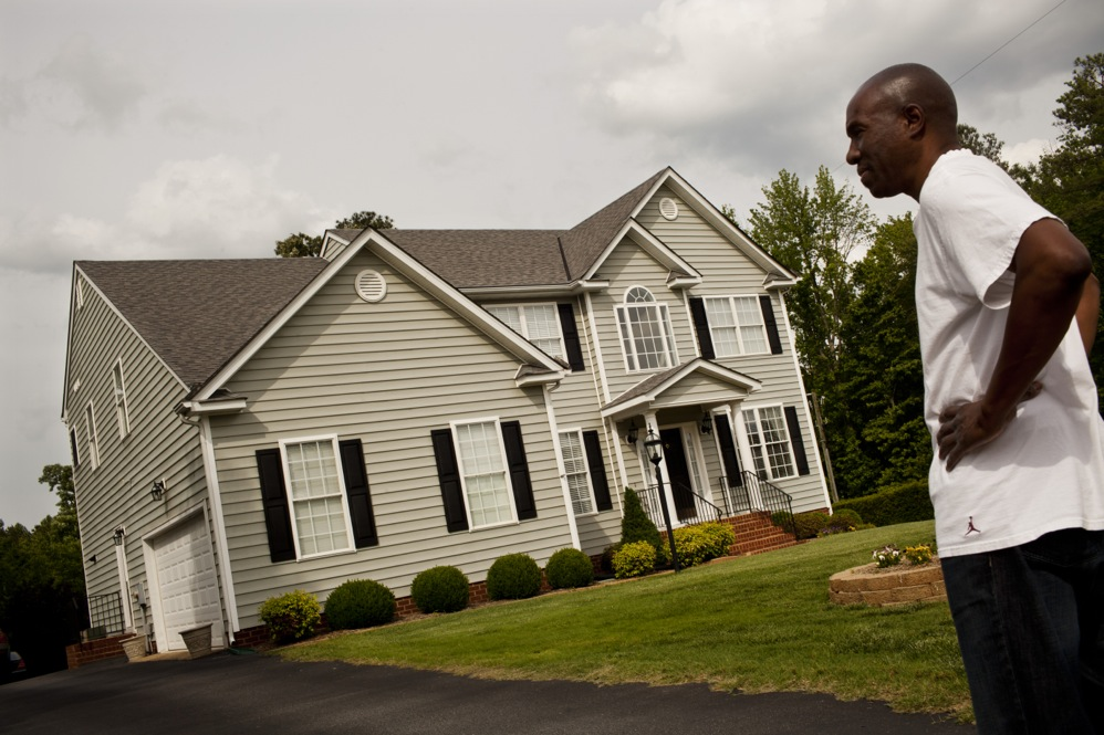 Frank stands outside his home in Glen Allen, Va., which he co-owned with his mother. The family recently sold the home in order to free up money for Ida's care.
