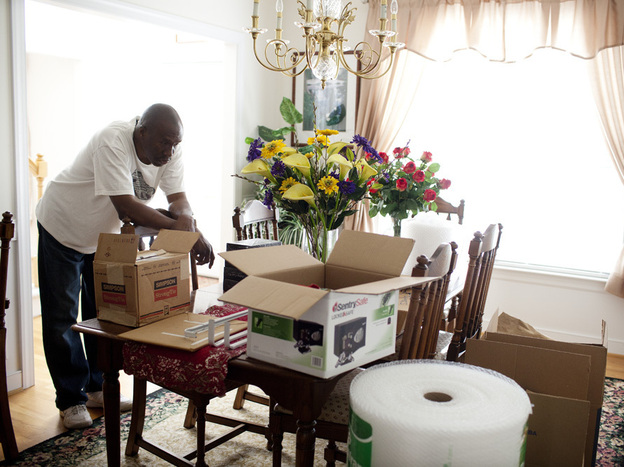 Frank Christian takes a break from packing in the dining room of his home in Glen Allen, Va., which he co-owned with his mother. The family recently sold the home in order to free up money for Ida's care.
