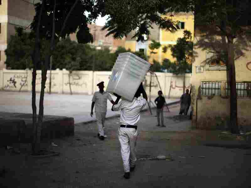A police officer carries empty ballot boxes to a polling station in Cairo. Turnout is expected to be heavy.