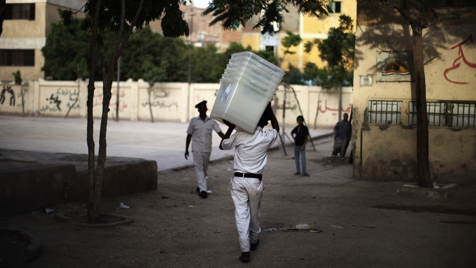 A police officer carries empty ballot boxes to a polling station in Cairo. Turnout is expected to be heavy. (AFP/Getty Images)