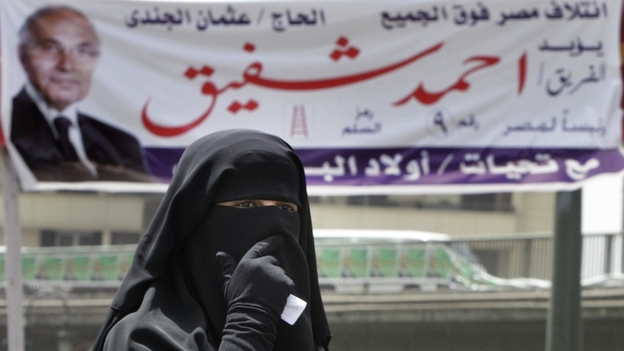 An Egyptian woman walks under a campaign banner in Cairo on Tuesday. Egypt holds its first competitive presidential election on Wednesday and Thursday, with a dozen candidates in the race. (AP)