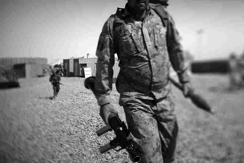 An Afghan policeman carries a rocket-propelled grenade launcher as he leaves for patrol on the outskirts of Marjah, near the Sistani Desert.
