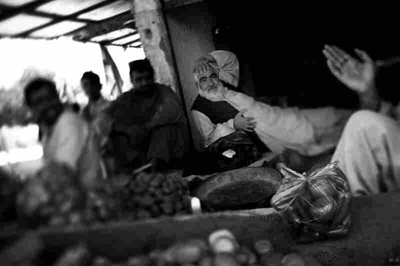 Today, the area is calm. Businessmen, farmers and shop owners gather for tea and conversation at a vegetable stand.